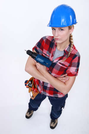 Aggressive female builder holding drill photo