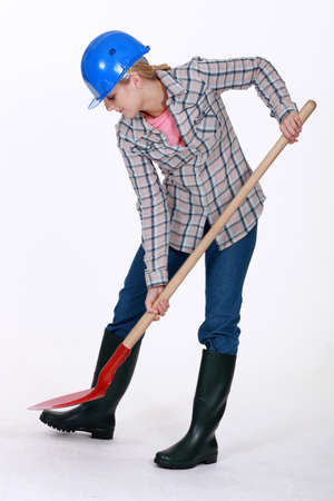 undermine: Woman digging with a shovel