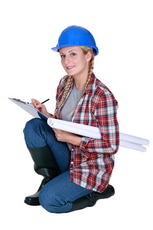 explanatory: Tradeswoman writing on a clipboard Stock Photo
