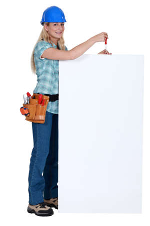 Tradeswoman holding a screwdriver over a blank sign Stock Photo - 14194493