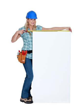 Tradeswoman measuring a blank sign Stock Photo - 14194413