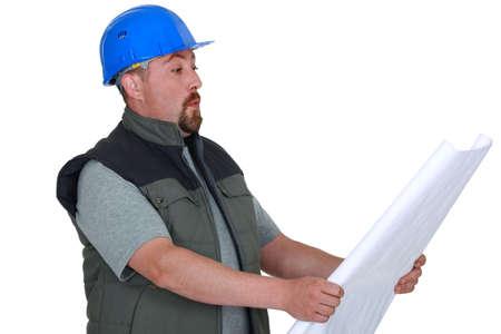taken: Surprised tradesman looking at a blueprint