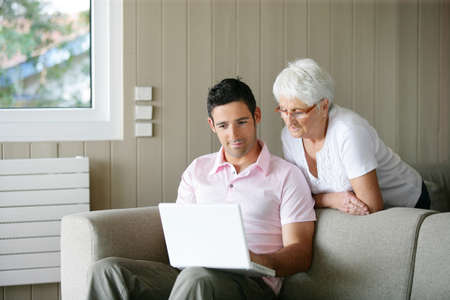 Young man and a senior woman looking at a laptop photo