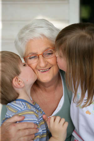 grandmother grandchild: Grandchildren kissing grandma Stock Photo
