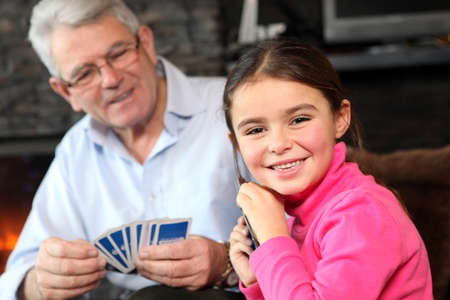 card game: Young girl playing cards with grandpa Stock Photo