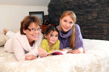 three generations: Mother, daughter and granddaughter reading book whilst laid on bed