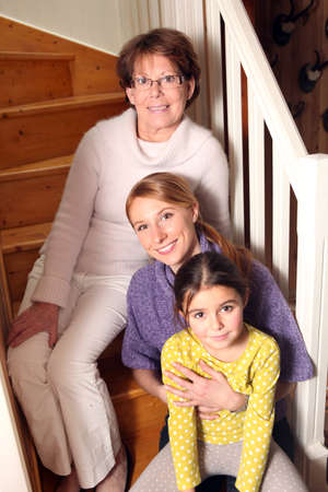 idea comfortable: grandmother, mother, and daughter sitting on stairs Stock Photo