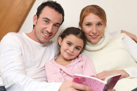 Parents reading a bedtime story to their daughter photo