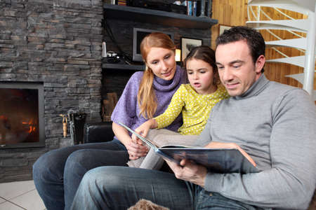 home heating: happy parents reading their young daughter a story