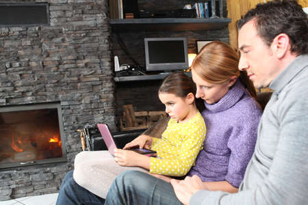 warm cloth: Family on a sofa in front of the fireplace Stock Photo