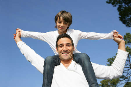 father and son: Child riding on his fathers shoulders