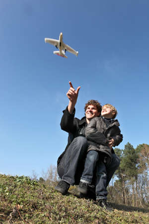 Father and son playing with toy plane in field photo