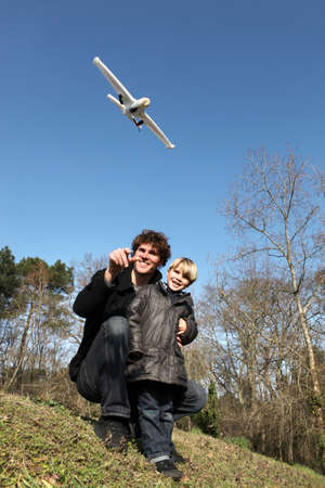 Father and son playing with an aeroplane photo