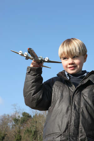monoplane: Little boy playing with toy plane Stock Photo