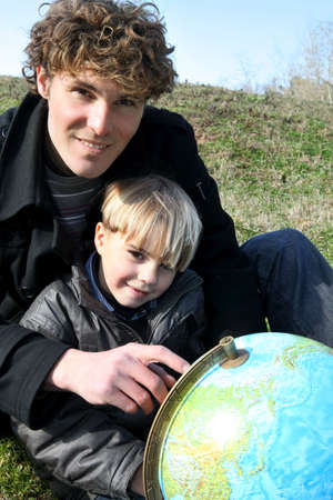 impart: Father and son looking at a globe Stock Photo