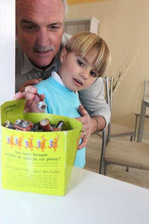Boy recycling batteries photo