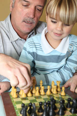 Young boy playing chess with his grandfather photo