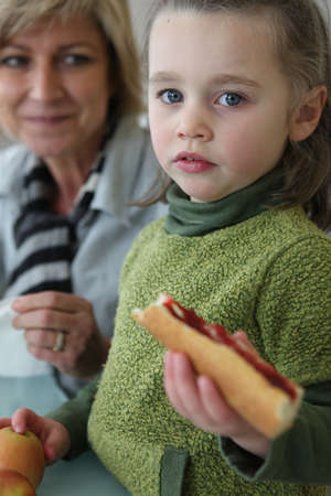 Little girl eating sandwich with mother photo