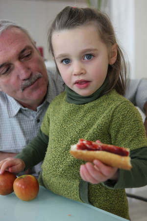 a little dinner: Little girl with grandfather eating sandwich