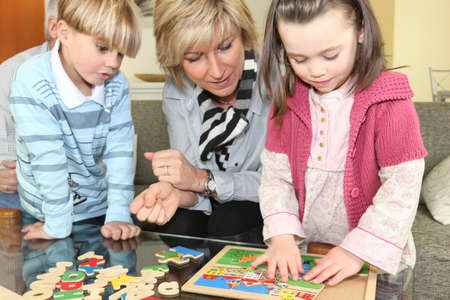Woman and children with a wooden puzzle photo