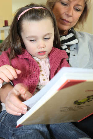 storytime: Little girl reading a book with her grandma Stock Photo
