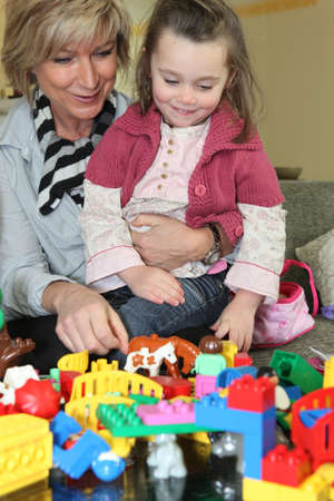 Mother and daughter playing with toys at home photo
