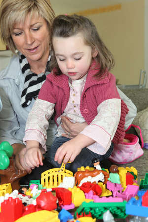 nurser: Little girl playing with her grandmother Stock Photo