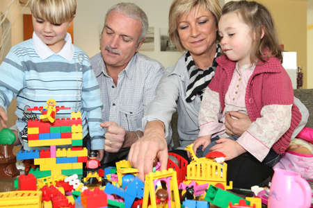 grandparents playing with grandchildren playing legos photo