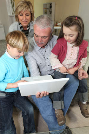 Couple looking at a laptop with their grandchildren photo