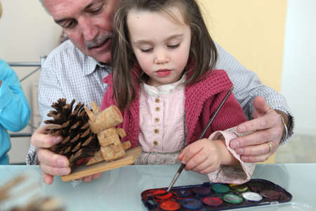 child care: Granddaughter and grandfather painting