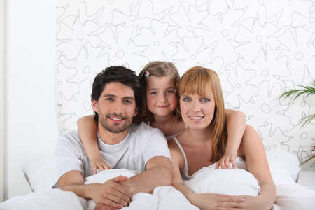 couple and their little girl in bed photo