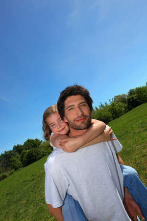 shoulder ride: Man carrying little girl on his back in a meadow Stock Photo