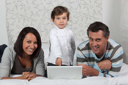 gratified: Parents and daughter on bed with computer Stock Photo