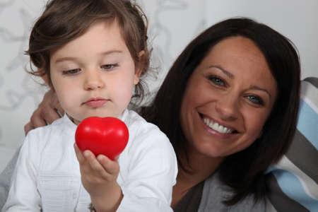 Little girl holding plastic heart Stock Photo - 14212926