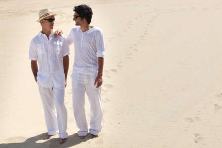 Grandfather and grandson walking in the sand photo