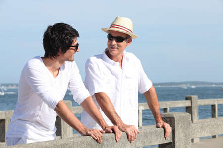 male bonding: Father and son stood on promenade Stock Photo