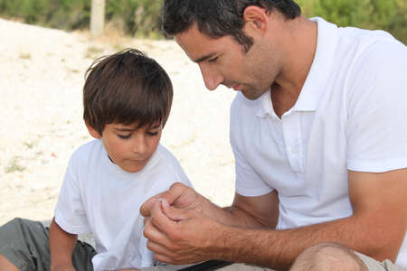 Father teaching son how to fish photo