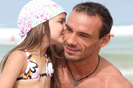 Girl giving dad a kiss photo