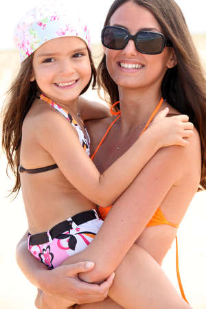 Mother and daughter at the beach together photo