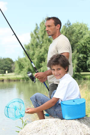 Father and son fishing at a lake photo