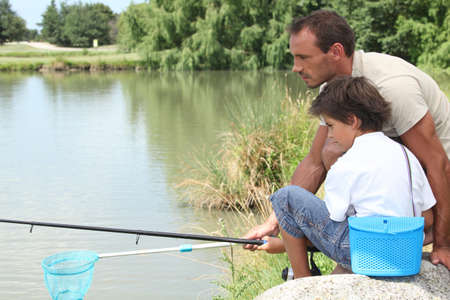 shore line: Father and son fishing together Stock Photo