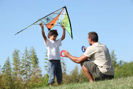 paternal: Father and son playing with a kite