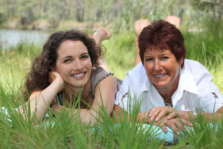 Older mother and adult daughter lying in the grass Stock Photo - 14214815
