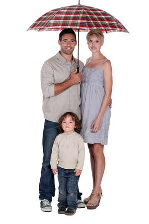 Family stood under umbrella photo