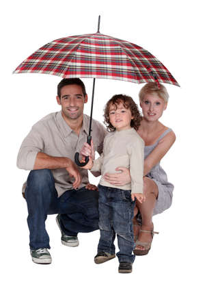 crouched: Young family sheltering under an umbrella