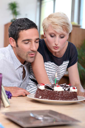 Couple blowing birthday candle photo