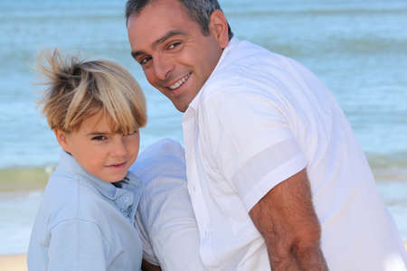 backward: Father and son on the beach