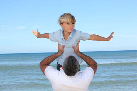 A father carrying his son by the beach. photo