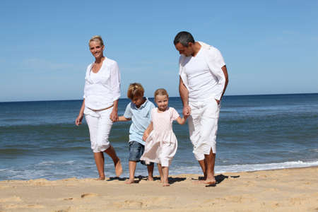 Beautiful family at the seaside in summertime photo
