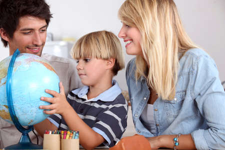 waxes: Parents with son and globe Stock Photo